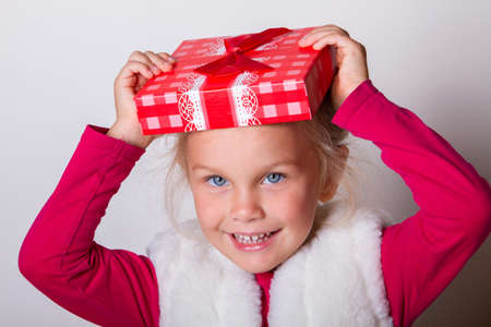 Portrait of an excited beautiful little girl wearing dress and sunglasses holding shopping bags isolated over light background