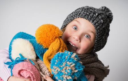 surprised excited little girl wearing knitted hat, scarf and sweater, holding a pile of hats, Child on light background. Fashion, choice, sale concept.