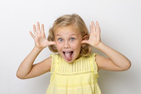 Kopf- und Handaufnahme eines kleinen Mädchens, das zum Spaß ihre Zunge in die Kamera streckt Standard-Bild