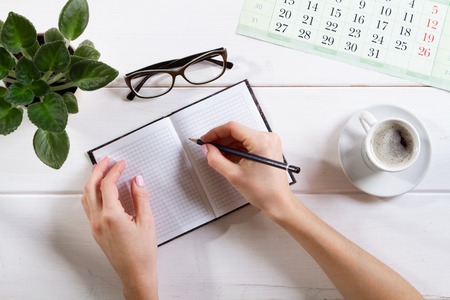 Maqueta para lista de verificación, manos femeninas están escribiendo en un cuaderno. sobre fondo claro. Concepto de oficina, escritor o estudio.