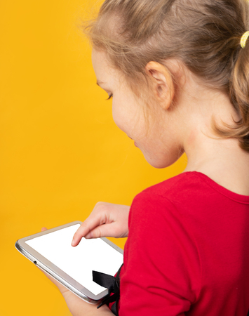 Cute little girl in red dress is using a digital tablet and smiling, standing on yellow background
