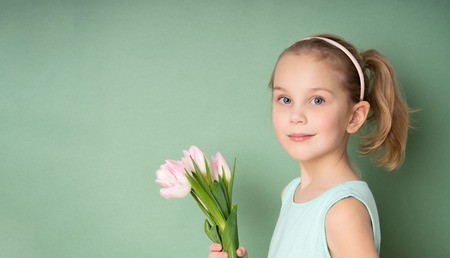 Adorable smiling little girl with tulips over green spring background Standard-Bild