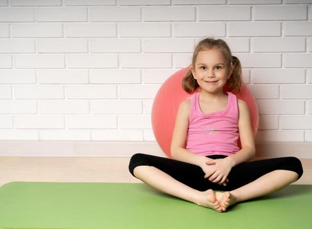 Cheerful little girl resting after sport exercises training on the mat at home, children's sports and yoga.
