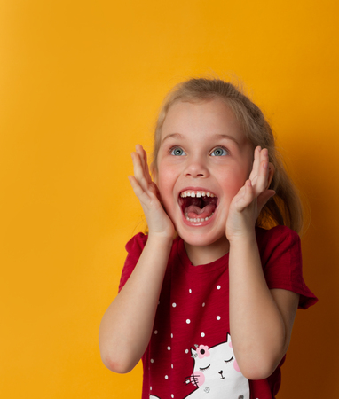 Image of excited screaming cute little standing isolated over yellow background. Looking away camera.