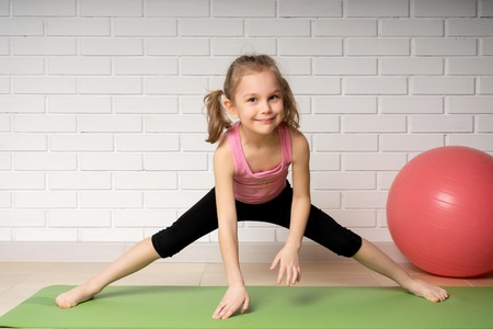 Cheerful little girl doing sports exercises on the mat at home, children's sports and yoga. Foto de archivo