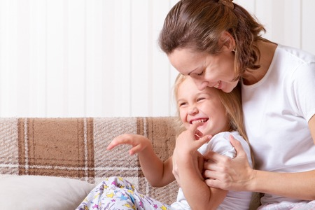daughter and mother at home, sitting on the couch, wearing pajamas, hugging and laughing 版權商用圖片