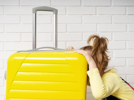 Portrait of a happy cheerful child tourist girl with a yellow suitcase for traveling, relaxing, peeking inside a bag and wondering content. New impressions from the trip
