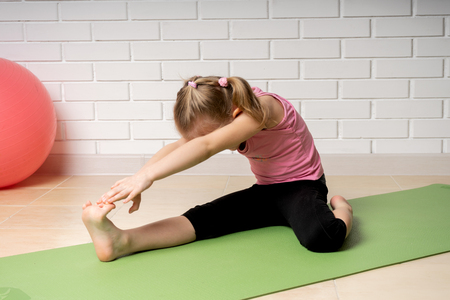 Cheerful little girl doing sports exercises on the mat at home, children's sports and yoga.