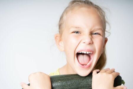 Little girl joyfully holds with zucchini laughing with open mouth on a white background. Healthy nutrition for children