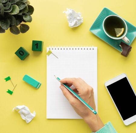 desktop with a mobile phone mockup, a cup of tea with lemon, chocolate, a notebook and a pencil. isolated on yellow top view, female hand makes notes in a notebook. Female table with accessories.
