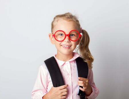 Little girl in glasses with school bag on the white background Imagens