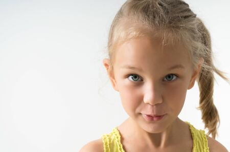 little blonde girl of 5 years old looks inquiringly in surprise at the frame, closeup isolated on a light background. Stock Photo