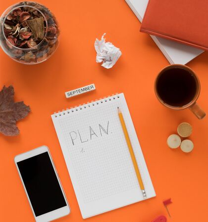 Modern color table office desk with notebook smartphone and other materials with a cup of tea and cookies, a notebook, a notebook page with the inscription PLAN in the middle. September. Autumn orange tones Banque d'images