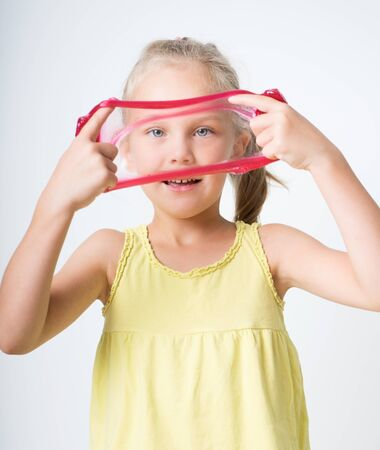 Happy joyful girl playing red slime. Girl stretches an elastic band slime lizun in different directions.