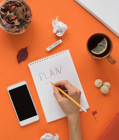 Modern color table office desk with notepad smartphone and other materials with a cup of tea. Blank notepad page for text entry in the middle. Top view, flat lay. Stock fotó
