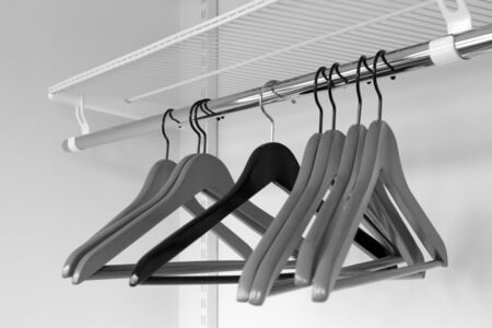 Clothes grey hangers in empty wardrobe, from black to middle. closeup
