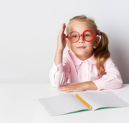 a schoolgirl with red glasses at a table with books pulls her hand to answer