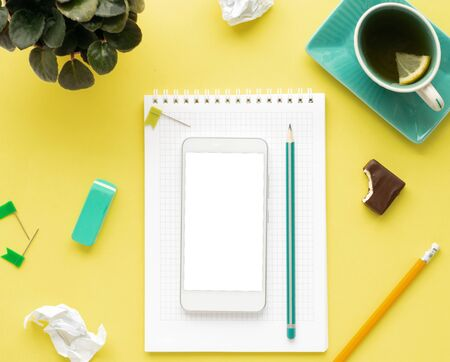 Stylized clean yellow desktop with smartphone with white screen, notebook, pencil and tea, workspace design, layout, top view, flat lay, copy space, close up