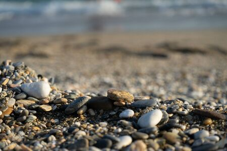 Wet sea pebbles and seashells on a wet sandy beach. Natural sea stones close-up. Beach smooth pebbles close-up. selective focus. Tourism and travel themed. Beach vacation background. 스톡 콘텐츠