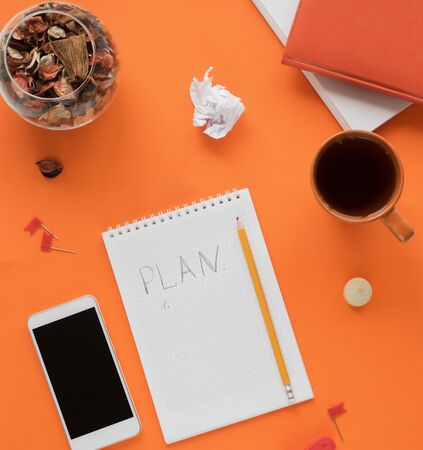 Modern color table office desk with notebook smartphone and other materials with a cup of tea and cookies, a notebook, a notebook page with the inscription PLAN in the middle. Top view, flat lay. Autumn orange tones