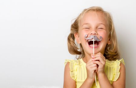 Free time for fun. Close up portrait of fancy, small girl with fake paper mustache cheerfully laughs isolated on grey background with copy space for text.