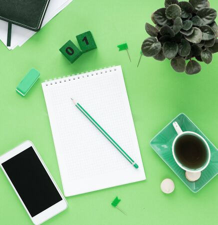table office desk with notepad smartphone and other materials with a cup of tea. Blank notepad page for text entry in the middle. Top view, flat lay. Green tones