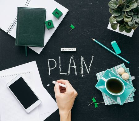 Woman hands writes a plan for autumn for September in desk Planning for the future. Top view on the desktop graphite stock. On the table is a notebook with a notebook, a cup of tea, canstovary, years,
