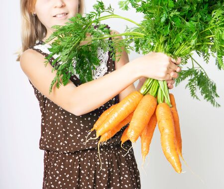 Cropped photo of teenager girl with a large armful of carrots with tops. Concept of healthy child nutrition
