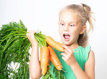 surprised little 6-year-old blonde holds a pack of fresh carrots with tops in her hands and is surprised at the size. 스톡 콘텐츠