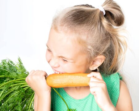 Little cute 6-year-old girl nibbles fresh eco carrots with tops. Healthy baby food concept 스톡 콘텐츠