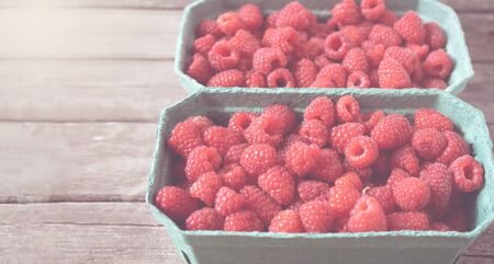 Fresh red raspberries in craft stalls, containers. on a wooden rustic old background. Top view of ripe berries. Autumn harvest. Toned