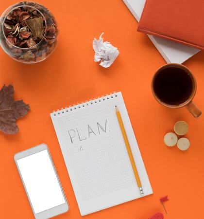 Colored office desk table with a smartphone notebook with a white screen and other materials with a cup of tea and cookies, a notebook, a notebook with the words PLAN in the center. Copy space. Autumn orange tones