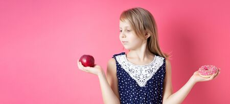 A picture of young girl choosing between red apple and donut