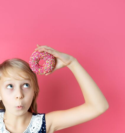 Surprised happy girl with a donut donut on a pink background. Close-up portrait with a funny teen girl with a donut. Makes mouse ears out of sweets