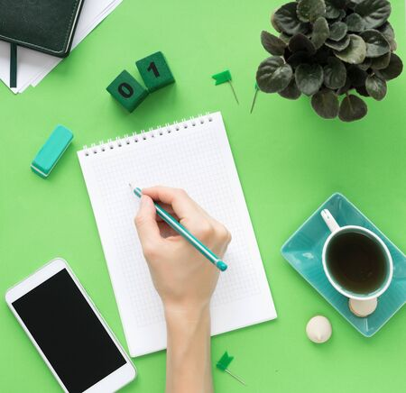 Female hand takes notes in a blank notebook page in the middle. Modern color table office desk with notepad smartphone and other materials with a cup of tea. Top view, flat lay. Green tones Фото со стока