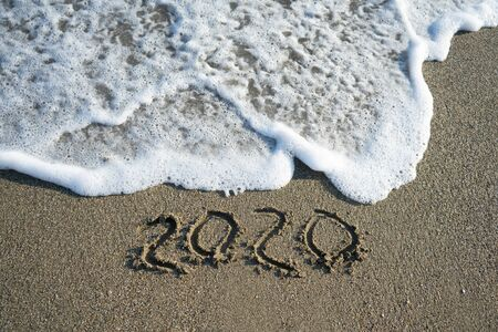 New year 2020 on sandy beach with waves.