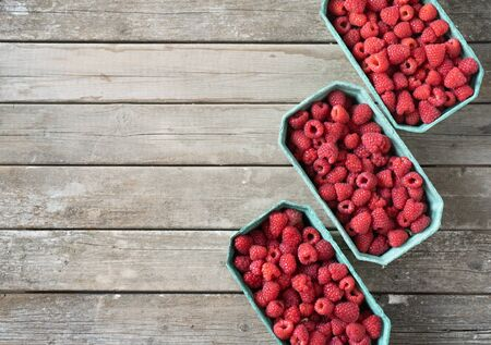 Fresh red raspberries in craft stalls, containers. on a wooden rustic old background. Top view of ripe berries. Autumn harvest.