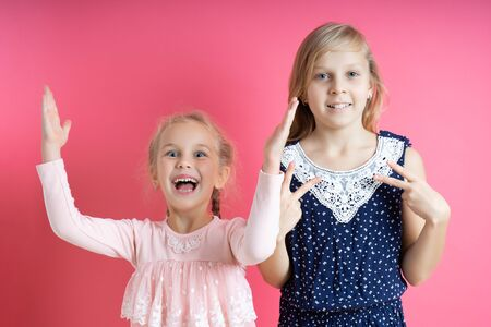 Two sisters laughing having fun show gestures on a pink background