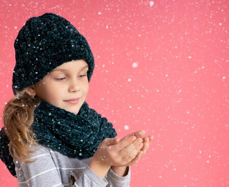 Happy toddler girl in a warm hat and scarf, standing under Christmas snow, caught a snowflake in her hands, enjoying a miracle on a pink background. Christmas and New Year concept.