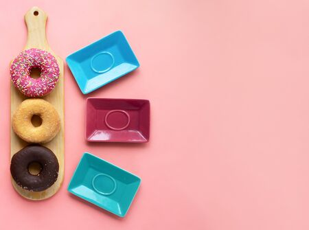 Three different donuts, chocolate donut, pink icing and without icing on a wooden cutting board ready to serve on saucers, on a pink background, top view with free space for your text