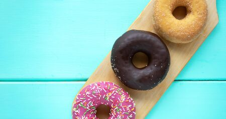 Three different donuts, chocolate donut, pink icing and without icing on a wooden cutting board on a wooden blue background, top view with free space for your text 스톡 콘텐츠