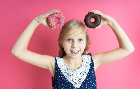 Funny happy girl with a donut donut on a pink background. Close-up portrait with a funny teen girl with a donut. Makes mouse ears out of sweets