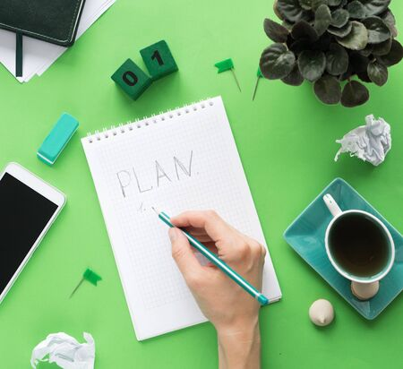 Female hand writes a plan in an empty notebook page in the middle. Modern color table office desk with notepad smartphone and other materials with a cup of tea. Top view, flat lay. Green tones