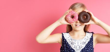 Playful girl holding donuts on her eyes. Close up portrait of a funny girl with long hair having fun with colorful donuts against her eyes. Satisfied child with a bandage on his hair, showing tongue.