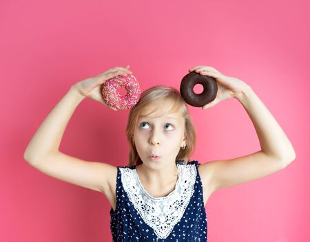 Funny happy girl with donut donuts on a pink background. Playful teenager girl holding donuts on her head. Woman shows a mouse. pink background