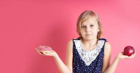 A picture of young girl choosing between red apple and donut. What to choose. doubt Standard-Bild