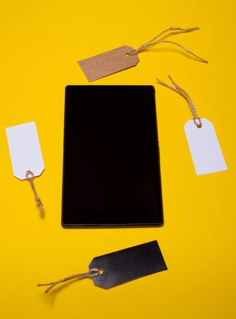 computer tablet and store tags. view from above on a yellow background. online shopping concept, sale, black Friday