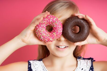Close up portrait of a funny girl with long hair having fun with colorful donuts against her eyes. Satisfied child with a bandage on his hair, showing tongue. Expressions, diet concept, vibrant colors