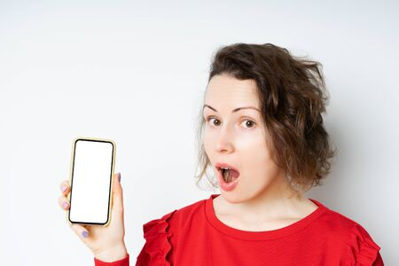 Surprised happy brunette woman in a red sweater showing a blank smartphone screen and pointing at him while looking at camera with open mouth over a light background. Standard-Bild