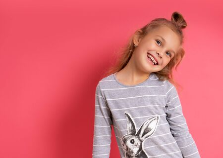 Funny little girl with a funny hairstyle in a striped sweater standing smiling on a pink background